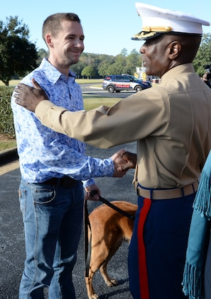 Former Marine Corps handler, David Pond (left), smiles and shakes hands with Col. James C. Carroll III (right), commanding officer, Marine Corps Logistics Base Albany, after officially adopting Pablo, a former military working dog with the base's, Marine Corps Police Department, during a ceremony held here, Dec. 15.
