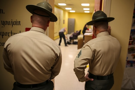 Sergeant Daniel E. Elizarraraz (left) and Sgt. Edwin A. GonzalezDawkins, drill instructors, Receiving Company, Support Battalion, wait for the last recruit to finish getting his hair cut during receiving at Marine Corps Recruit Depot San Diego, Dec. 15. Recruits receive haircuts immediately after arriving to create uniformity. Today, all males recruited from west of the Mississippi are trained at MCRD San Diego. The depot is responsible for training more than 16,000 recruits annually. India Company is scheduled to graduate March 11.