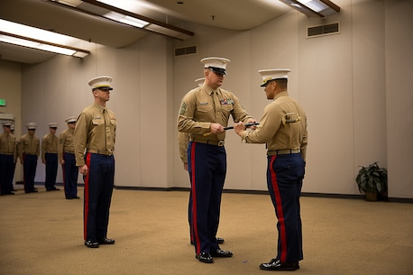 Sgt. Maj. Kent Cartmill (center), the outgoing senior enlisted leader of Marine Corps Recruiting Station Seattle, returns the sword of office to Maj. Sung Kim, his commanding officer, during a passage of command ceremony in Seattle Dec. 12, 2015. During the ceremony, Cartmill, from Garden City, Kan., was awarded a Meritorious Service Medal and relinquished duties to Sgt. Maj. Jeffrey Dagenhart. (U.S. Marine Corps photo by Sgt. Reece Lodder)