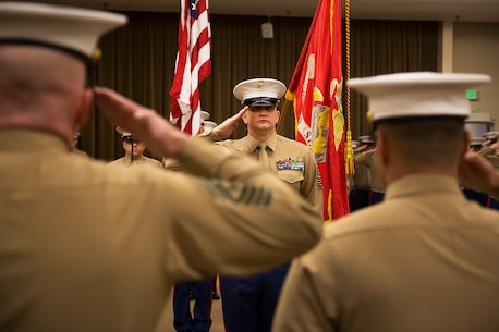 Sgt. Maj. Kent Cartmill (center), the outgoing senior enlisted leader of Marine Corps Recruiting Station Seattle, renders honors to Maj. Sung Kim, the commanding officer, during a passage of command ceremony in Seattle Dec. 12, 2015. During the ceremony, Cartmill, from Garden City, Kan., was awarded a Meritorious Service Medal and relinquished duties to Sgt. Maj. Jeffrey Dagenhart. (U.S. Marine Corps photo by Sgt. Reece Lodder)