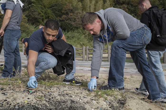 Sgts. Christian Lopezsilva, left, and Josh Hood, avionics technicians with Marine Attack Squadron 214, pick up trash on Katazoe Beach on Oshima Island, Japan, during the Oshima Beach Cleanup Dec. 12, 2015. Coordinated by the Single Marine Program and the Marine Aircraft Group 12 Chaplain's office, the cleanup not only helped beautify the local community, but also gave service members from Marine Corps Air Station Iwakuni the opportunity to explore Japan.