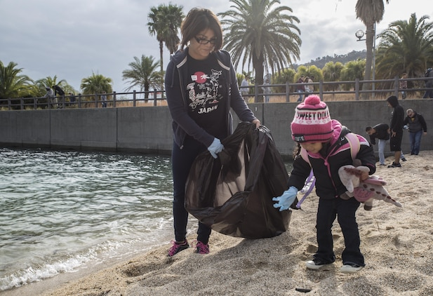 Sgt. Susana Ramirez, a food service specialist with Marine Wing Support Squadron 171, and her daughter Aaliyah, collect debris at Katazoe Beach on Oshima Island, Japan, during the Oshima Beach Cleanup Dec. 12, 2015. Approximately 90 volunteers helped with the cleanup organized by Marine Aircraft Group 12 Chaplain's office and the Single Marine Program at Marine Corps Air Station Iwakuni.