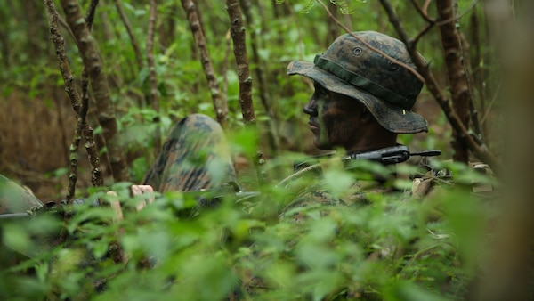 Corporal Jordan Clymer, from Mt. Ayer, Iowa, and assistant radio operator with Company A, 1st Reconnaissance Battalion, 1st Marine Division, rests during reconnaissance and surveillance training, Nov. 19-21, 2015, aboard Marine Corps Training Area Bellows, Hawaii. The Marines conducted insertion, infiltration, execution, exfiltration, and extraction in terrain unfamiliar to what is usually found at their home base in California. The Hawaiian terrain ranged from beach shores, to dense jungle and open valleys during pouring rains.