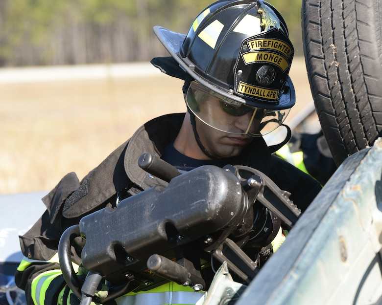 Edward Monge, 325th Civil Engineering Squadron firefighter, uses the jaws-of-life to pry open a crashed car door during a vehicle extrication exercise.  The firefighters of the 325th CES ensure the safety of all of Tyndall's service members, civilians, and contractors. (U.S. Air Force photo by Airman 1st Class Cody R. Miller/Released)
