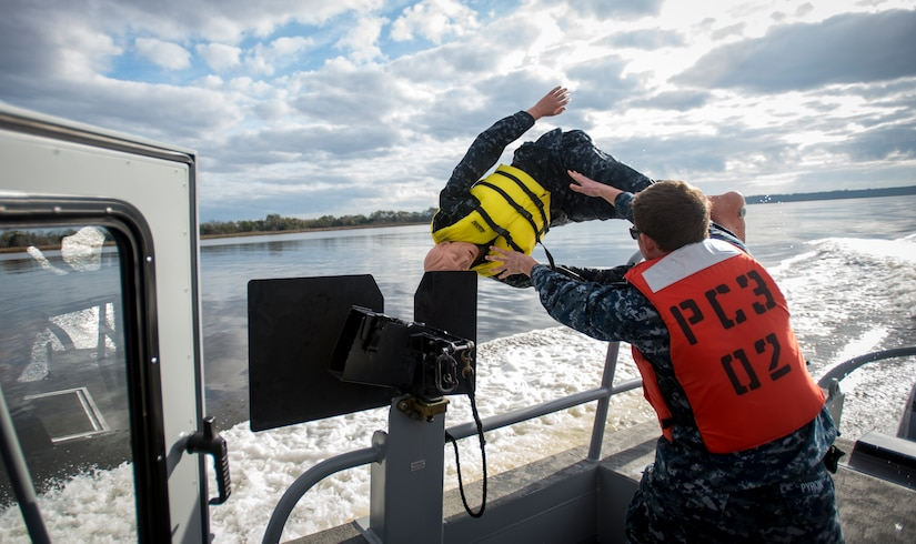 A Sailor from the harbor patrol unit simulates a man-overboard exercise Dec. 9, 2015, on the Cooper River near Joint Base Charleston – Weapons Station, S.C. JB Charleston's port operations recently implemented a new training program to effectively cut down on spending and improve resourcefulness. The training consisted of putting Sailors through a series of classes. The week following their classes, the new trainers were put to the test instructing the newer Sailors on the information they just learned. (U.S. Air Force photo/Senior Airman Clayton Cupit)