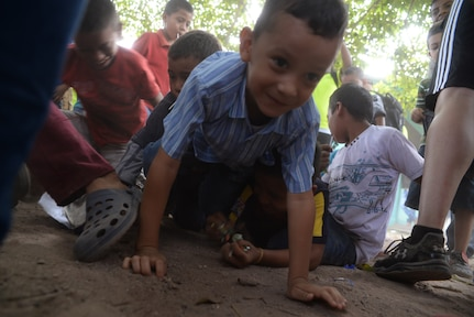 A Honduran boy grabs candy that fell from a piñata during Chapel Hike 65, Honduras, Dec. 12, 2015. Chapel hikes like this one help build bonds with local communities. (U.S. Air Force photo by Senior Airman Westin Warburton/Released)