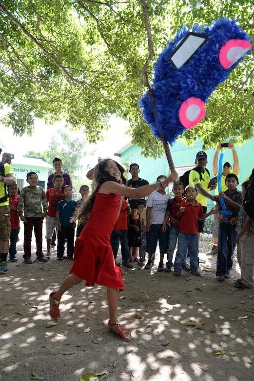 A Honduran girl strikes a piñata during Chapel Hike 65, Honduras, Dec. 12, 2015. Chapel hikes like this one help build bonds with local communities. (U.S. Air Force photo by Senior Airman Westin Warburton/Released)