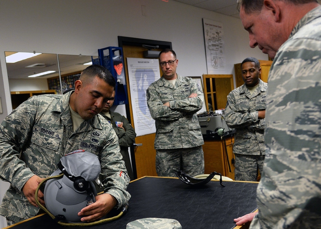 Tech. Sgt. Louis Soriano, a member of the 149th Operations Group, shows Maj. Gen. James Hecker, 19th Air Force commander, the capabilities of a pilot's helmet mounted with integrated targeting technology at the aircrew flight equipment section during the general's visit to Joint Base San Antonio-Lackland, Texas, Dec. 10.