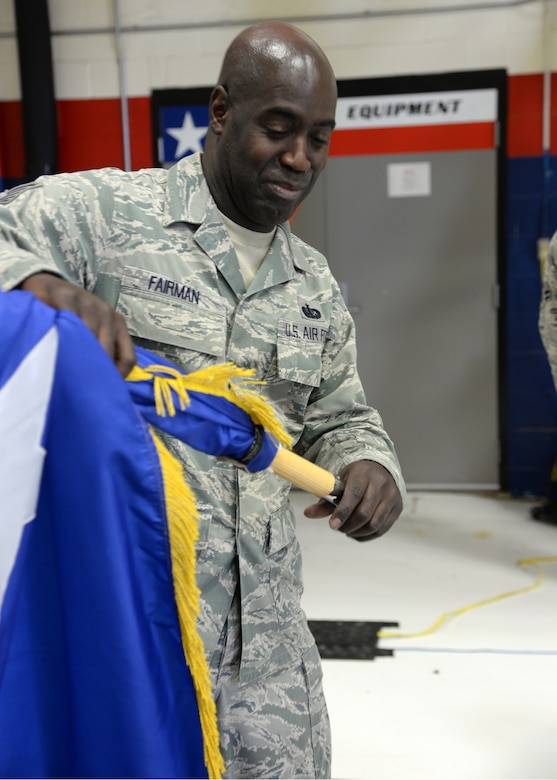 Tech. Sgt. Kevin Fairman, a member of the 149th Fighter Wing, puts away a two-star command flag after an all call held Dec 10 in a maintenance hangar at Joint Base San Antonio-Lackland, Texas.