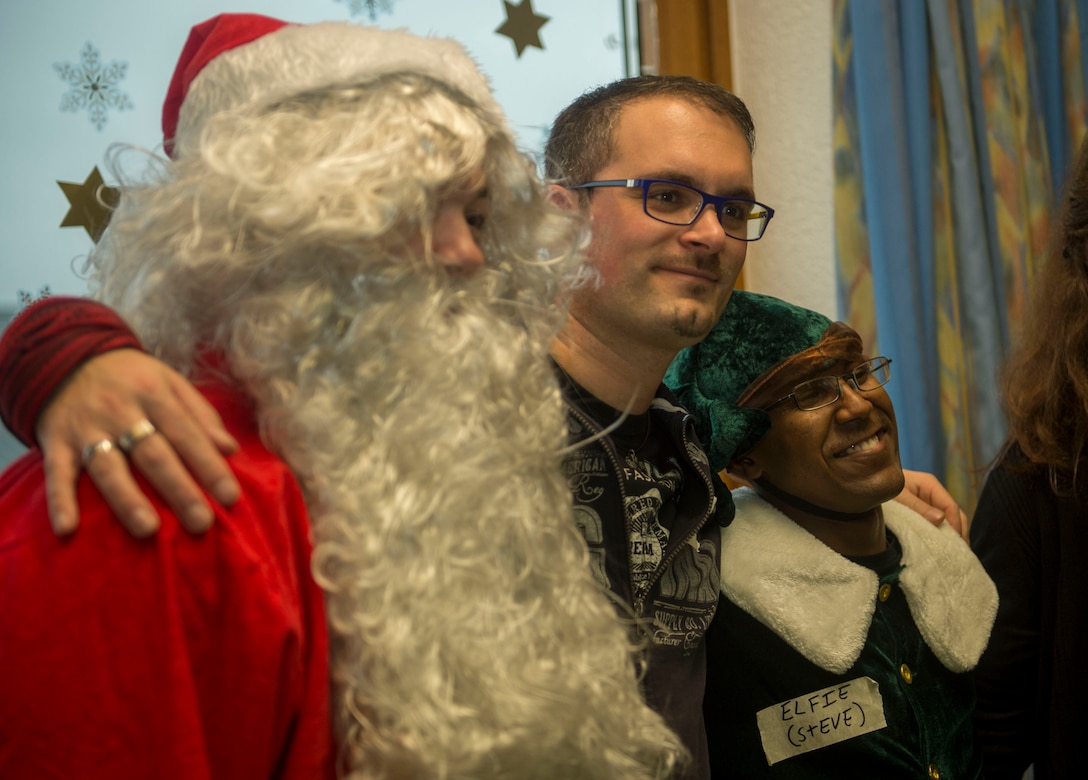 Dr. Alexander Knauff, University of Trier professor of social work and sciences and St. Vinzenzhaus caretaker, poses for a photo with Santa Claus and an elf during a holiday party at the institution of child and youth services in Speicher, Germany, Dec. 13, 2015. Volunteers from Spangdahlem Air Base's First Four group selected two individuals to dress as Santa Claus and a Christmas elf to entertain the children. (U.S. Air Force photo by Airman 1st Class Timothy Kim/Released)