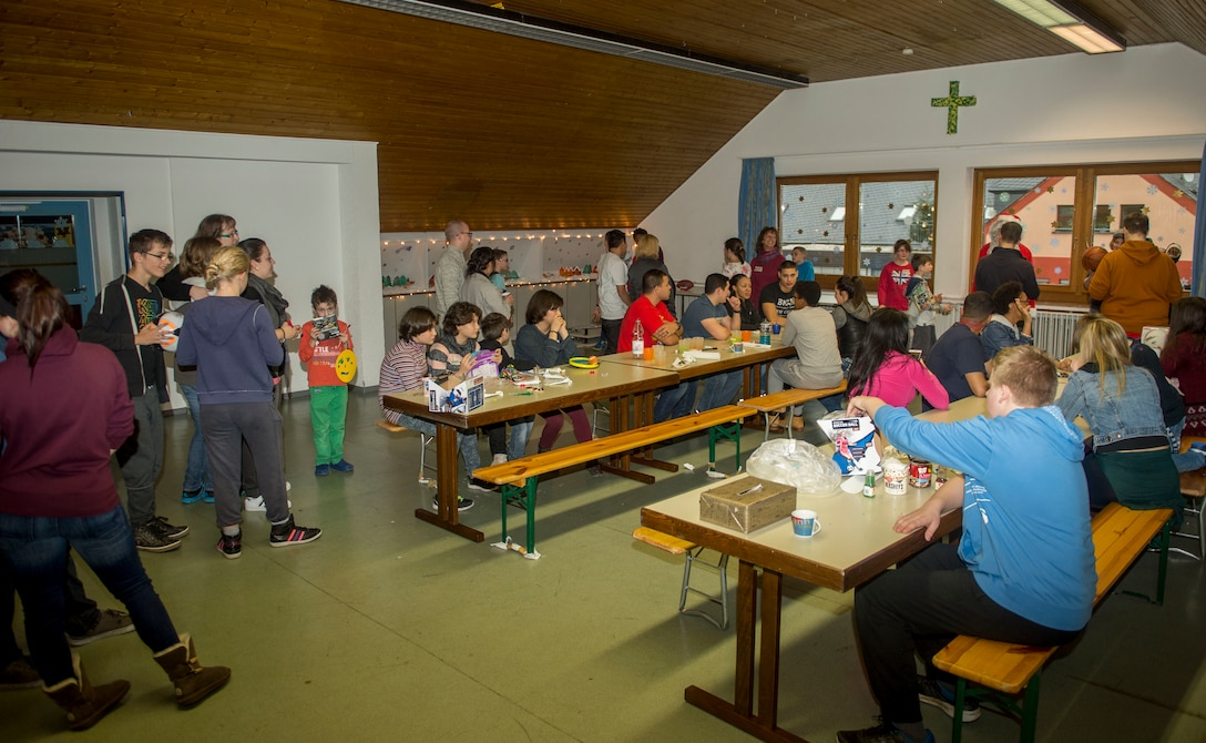 First Four volunteers from the 52nd Fighter Wing and St. Vinzenzhaus residents participate in a holiday party at the institution of child and youth services in Speicher, Germany, Dec. 13, 2015. Spangdahlem Air Base's First Four volunteers coordinated an arts-and-craft activity booth and designed cookies with the residents. (U.S. Air Force photo by Airman 1st Class Timothy Kim/Released)