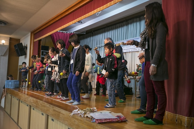 Participants practice using the kendama on stage during Cultural Day in Tsuzu, Dec. 12, 2015. This cultural exchange provides both the American and Japanese communities an opportunity to interact, learn about each other's culture, and make new friends through a variety of activities.