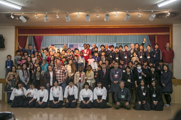 Participants pose for a group photo at the end of Cultural Day in Tsuzu, Japan, Dec. 12, 2015. The event provides both the American and Japanese communities an opportunity to interact, learn about each other's culture, and make new friends through games, food, and arts and crafts. Visitors participated in a variety of activities such as mochi pounding, making wooden flutes, walking on bamboo stilts, and much more.