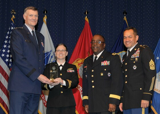DLA director Air Force Lt. Gen. Andy Busch, left, presents Navy Lt. Jill Corrales, retail manager at Distribution Cherry Point, N.C., with the Company Grade Officer of the Year award at the 48th annual employee recognition ceremony Dec. 10.  Distribution's commander Army Brig. Gen. Richard Dix, second from right, and DLA's Senior Enlisted Leader Army Command Sgt. Maj. Charles Tobin, right, were also on-hand to present the award.