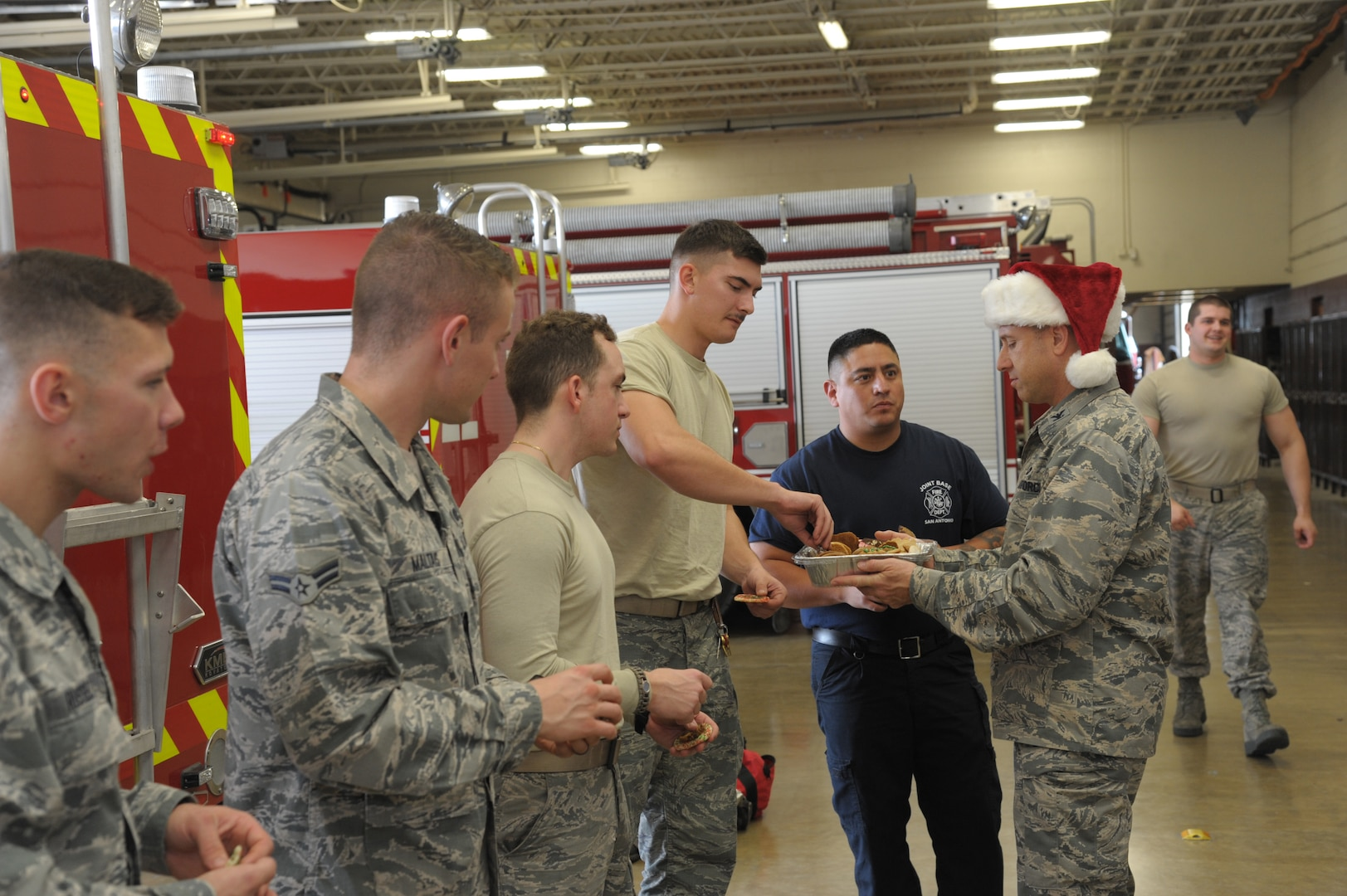 Col. Michael Gimbrone (right), 502nd Security Forces Logistics Support Group commander, delivers Christmas cookies to 502nd Civil Engineer Squadron firefighters Dec. 11 at JBSA-Randolph.