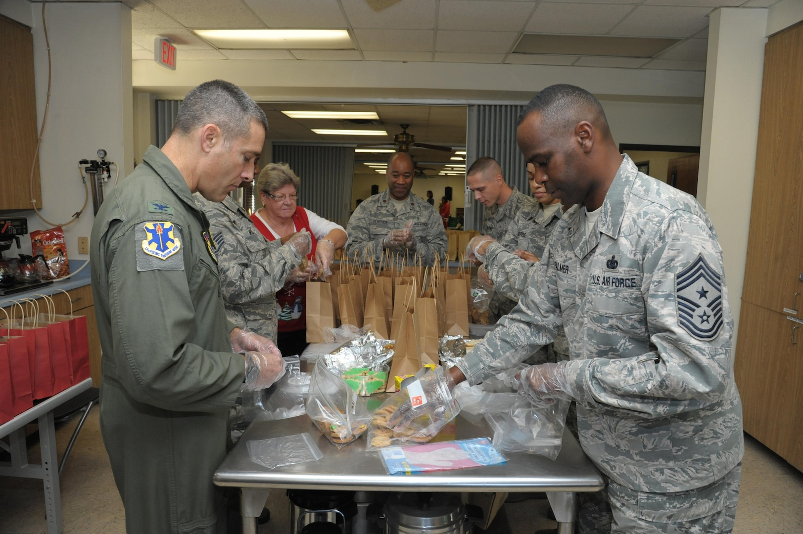 Col. Matthew Isler (left), 12th Flying Training Wing commander, and Chief Master Sgt. Troy Palmer, 12th FTW command chief, along with other JBSA-Randolph members, help bag cookies Dec. 9 during the cookie drive at Joint Base San Antonio-Randolph. The program provides baked goods to single Airmen who otherwise may not get home-cooked treats during the holidays.