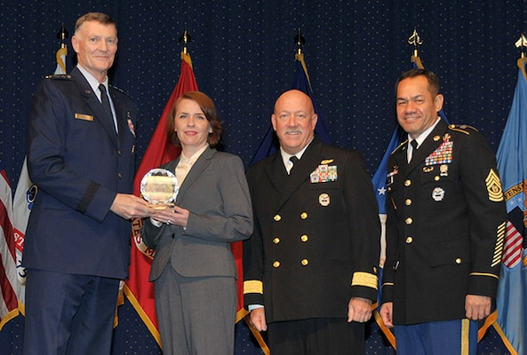 DLA Director Air Force Lt. Gen. Andy Busch presents a DLA Outstanding Personnel of the Year award to Natalya Radyk, Maritime Supplier Operations, at the 48th Annual DLA Employee Recognition Ceremony Dec. 10 at the McNamara Headquarters Complex in Ft. Belvoir, Va. Pictured with Busch and Radyk is Land and Maritime commander Navy Rear Adm. John King, and Army Command Sgt. Maj. Charles Tobin, DLA's senior enlisted leader.