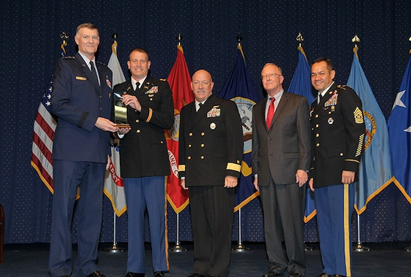 DLA Director Air Force Lt. Gen. Andy Busch presents the DLA Joint Reserve Forces Junior Officer of the Year award to Army Capt. Vince Barber at the 48th Annual DLA Employee Recognition Ceremony Dec. 10 at the McNamara Headquarters Complex in Ft. Belvoir, Va. Pictured with Busch and Barber is Land and Maritime commander Navy Rear Adm. John King, Robert A. McCullough, DLA Deputy Director J9, Joint Reserve Force, and Army Command Sgt. Maj. Charles Tobin, DLA's senior enlisted leader.