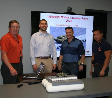 Dr. Jimmy Fowler and Dr. Mark Wahl  explaining the table model and briefing the Lightweight Modular Causeway System (LMCS) to MAJ Wallace Mattos, the Military Personnel Exchange Program Officer.  Also shown is Bo Tennant, Security.  MAJ Mattos was  learning about the program to support his upcoming mission representing ERDC in Brazil.