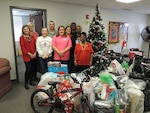Air Force Col. Rob Bloker, industrial support activity commander for DLA Aviation at Warner Robins, Georgia, poses with DLA Aviation employees next to gifts they collected Dec. 11, 2015 for 30 Salvation Army Christmas angels.