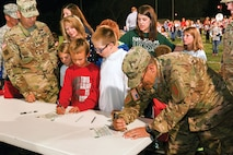 "Lt. Col. Brad Duplessis, right, 5th Squadron, 4th Cavalry Regiment, 2nd Armored Brigade Combat Team, 1st Infantry Division, signs his name to a charter declaring the partnership between his squadron and Unified School District 473 Oct. 9 at Chapman, Kansas. Duplessis said, ""It's about people and you have to form a relationship and what we did is we tried to say, 'Hey, we are on your team.'"""