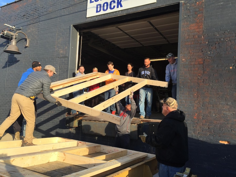 The team pitches in to load a wall frame constructed at the Habitat for Humanity workshop for transport to the construction site.