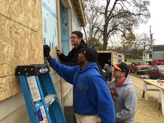 Master Sgt. Kelvin France, Chris Brackett (rear), and Bjorn Hale (right) install siding on a Habitat for Humanity home during a Corps service outing Nov. 21, 2015.