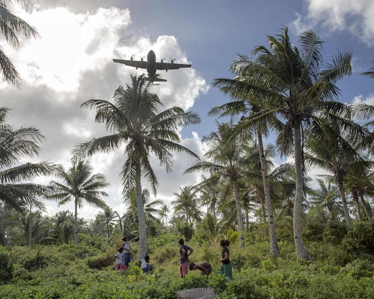 Islanders watch a C-130 Hercules fly overhead during Operation Christmas Drop 2015 at Fais Island, Federated States of Micronesia, Dec. 8, 2015. A C-130 assigned to the 36th Airlift Squadron delivered over 800 pounds of supplies to the island during the operation. This year marked the first ever trilateral Operation Christmas Drop where the Air Force, Japan Air Self-Defense Force and the Royal Australian Air Force worked together to provide critical supplies to 56 Micronesian islands. (U.S. Air Force photo/Osakabe Yasuo)
