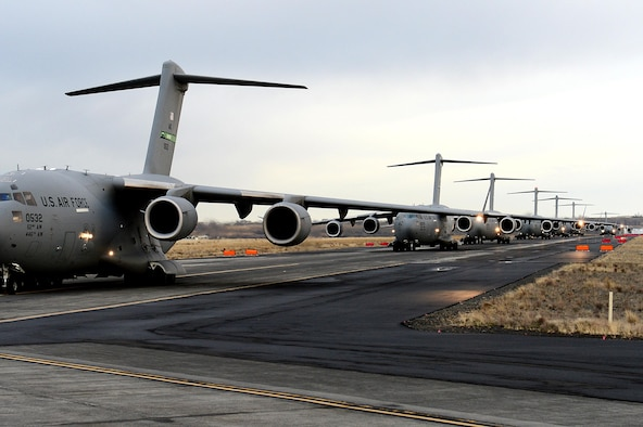 Eleven C-17 Globemaster IIIs line up on the runway at Moses Lake, Wash., after an airdrop during exercise Rainier War Dec. 10, 2015. Rainier War is a semiannual large formation exercise, hosted by the 62nd Airlift Wing, designed to train aircrews under realistic scenarios that support a full spectrum operations against modern threats and replicate today's contingency operations. (U.S. Air Force photo/Senior Airman Divine Cox)