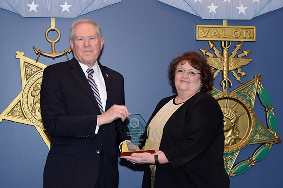 The Under Secretary of Defense for Acquisition, Technology, and Logistics, the Honorable Frank Kendall hosts the 2015 Defense Acquisition Workforce awards at the Pentagon, Arlington Va., Dec 10,2015.DLA Aviation's Supplier Operations Directorate's Technical Quality Supervisor Marsha Barron receives the Individual Achievement Award in Production, Quality, and Manufacturing.(U.S. Army photo by Mr. Leroy Council, AMVID/Released)