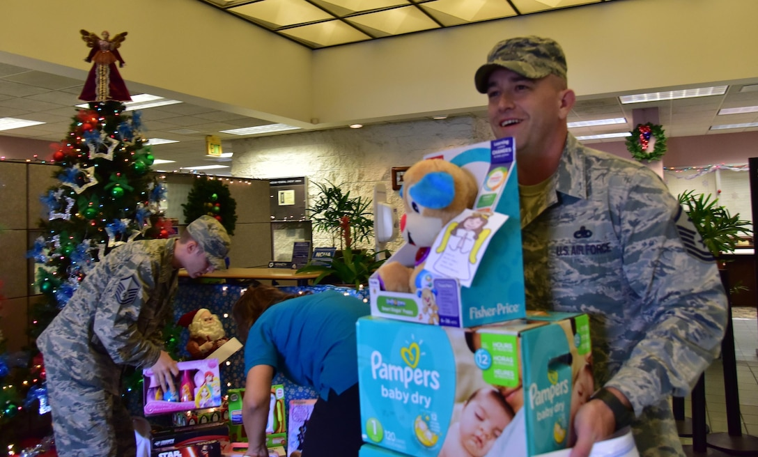 MSgt Jacob Davidson, First Sergeant, 647th Civil Engineering Squadron, carries donations to the Angel Tree program to his vehicle on Joint Base Pearl Harbor-Hickam  Dec. 17, 2015. The Angel Tree program, which provides monetary assistance and gifts to Airmen, is a seasonal charitable program ran by members of Operation Warmheart. (U.S. Air Force photo by Staff Sgt. Christopher Stoltz)