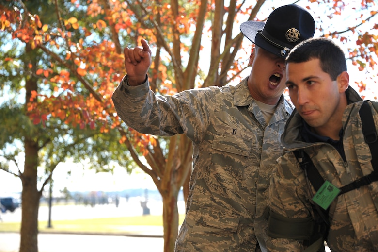 Tech. Sgt. Chi Yi welcomes a cadet to Officer Training School at Maxwell Air Force Base, Nov. 13, 2013. Yi serves as a Military Training Instructor for OTS. (U.S. Air Force Photo by Senior Airman William Blankenship)