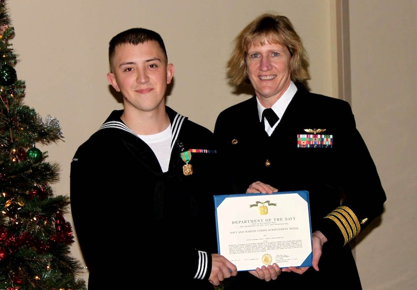 Seaman Colby Johnson, a general hospital corpsman serving at Naval Health Clinic Charleston, receives a Navy and Marine Corps Achievement from NHCC Commanding Officer Capt. Elizabeth Maley Dec. 4 at the clinic. Johnson was honored for saving the life of a baby who lost consciousness while choking Halloween night at Joint Base Charleston – Weapons Station. (Navy photo/ Petty Officer 3rd Class Robert Jackson)