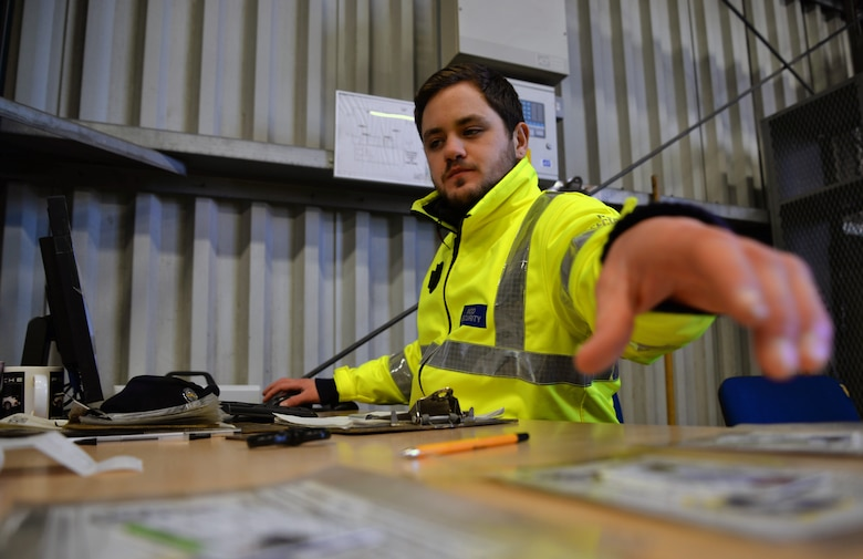 Sam Bannister, 100th Security Forces Squadron/Ministry of Defence civilian security officer, grabs a visitor's photo ID and base pass Dec. 9, 2015, at the search barn on RAF Mildenhall, England. On an average day, officers inspect anywhere from 160 to 300 vehicles. Members inspect a range of cars including heavy-goods vehicles, contracting staff and visitors to the base. (U.S. Air Force photo by Senior Airman Christine Halan/Released)