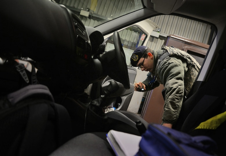 U.S. Air Force Airman Ryan Griffith, 100th Security Forces Squadron response force leader, inspects a vehicle Dec. 15, 2015, at the search barn on RAF Mildenhall, England. Both an armed Airman and a Ministry of Defence Guard Service civilian security officer are required to be in attendance during a vehicle inspection. (U.S. Air Force photo by Senior Airman Christine Halan/Released)