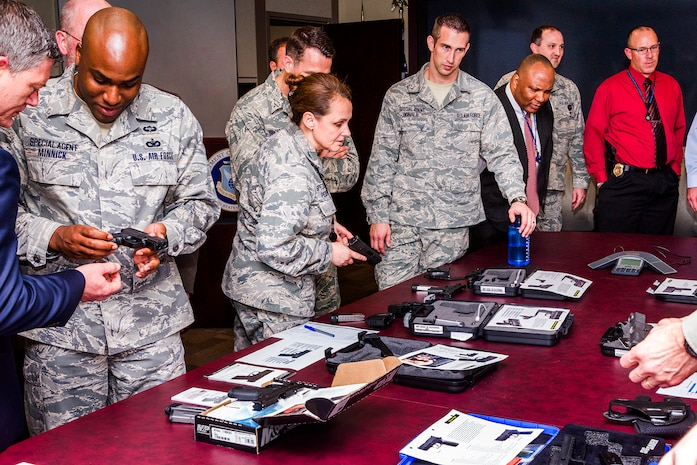 Air Force Office of Special Investigations members check out a display table of privately owned weapons Dec. 10 at OSI headquarters. The 10 guns showcased some of the options available to Special Agents who want to carry a POW in accordance with new OSI Weapons Program policy guidance. (U.S. Air Force photo by Michael Hastings)