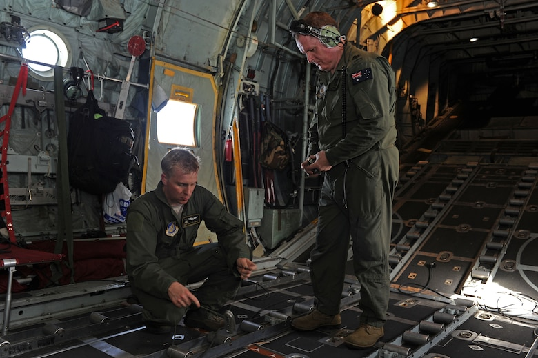 151211-N-ZB122-010 U.S. Air Force Staff Sgt. Ren Forbes, 36th Airlfist Squadron loadmaster (right), and Royal Australian Air Force Warrant Officer Rod Cairns (left) perform post-flight duties after successfully dropping multiple bundles to islands in the Federated States of Micronesia during Operation Christmas Drop, Dec. 11, 2015. Operation Christmas Drop is the Department of Defense's longest running humanitarian airdrop mission where C-130 crews drop LCLA bundles filled with donated goods and supplies for 56 islands throughout the Commonwealth of the Northern Marianas, Federated States of Micronesia and Republic of Palau. This year marks the first ever trilateral execution that includes air support from the Japan Air Self-Defense force and Royal Australian Air Force C-130 crews. (U.S. Navy photo by Mass Communication Specialist 2nd Class Chelsy Alamina)