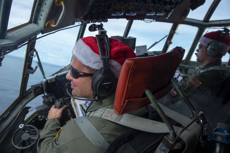 Crew members with the 36th Airlift Squadron fly over Ettal Atoll, Federated States of Micronesia, Dec. 9, 2015, during Operation Christmas Drop. This is a Humanitarian Aid/Disaster Relief training event where C-130 aircrews perform low-cost low-altitude airdrops on unsurveyed drop zones while providing critical supplies to 56 islands throughout the Commonwealth of the Northern Marianas, Federated States of Micronesia and Republic of Palau. It highlights the U.S. and allied airpower capabilities to orient and respond to activities in peacetime and crisis. In addition to delivering critical supplies to those in need, Operation Christmas Drop provides specific training to U.S. and allied aircrews, enabling theater-wide airpower. (U.S. Air Force photo by Osakabe Yasuo/Released)