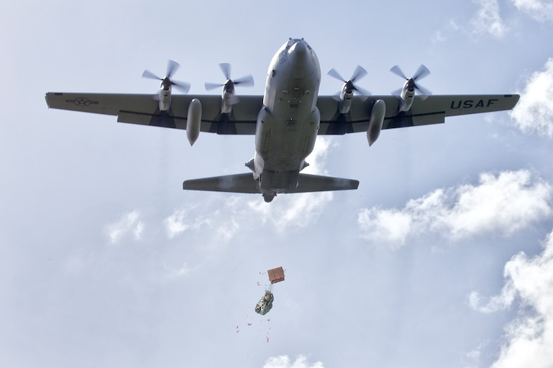 A C-130 Hercules assigned to the 36th Airlift Squadron drops a bundle filled with donated goods and supplies during Operation Christmas Drop 2015, at Fais island, Federated States of Micronesia, Dec. 8, 2015. Airmen delivered over 800 pounds of supplies to the island of Fais during the drop. This year marks the first trilateral Operation Christmas Drop where the U.S. Air Force, Japan Air Self-Defense Force and the Royal Australian Air Force work together to provide critical supplies to 56 Micronesian islands impacting 20,000 islanders. (U.S. Air Force photo by Osakabe Yasuo/Released)