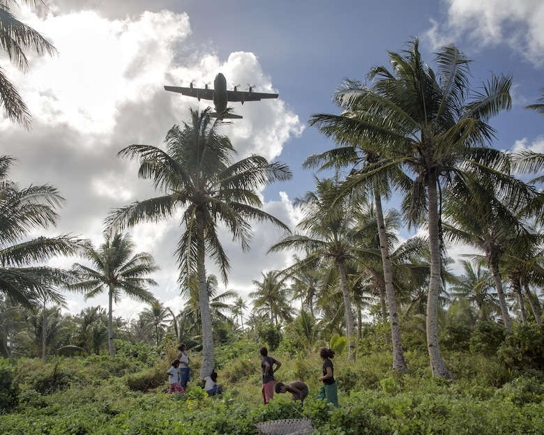 Islanders from Fais watch a C-130 Hercules fly over head during Operation Christmas Drop 2015, at Fais island, Federated States of Micronesia, Dec. 8, 2015. A C-130 Hercules assigned to the 36th Airlift Squadron delivered over 800 pounds of supplies to the island of Fais during Operation Christmas Drop 2015. This year marks the first ever trilateral Operation Christmas Drop where the U.S. Air Force, Japan Air Self-Defense Force and the Royal Australian Air Force work together to provide critical supplies to 56 Micronesian islands.(U.S. Air Force photo by Osakabe Yasuo/Released)