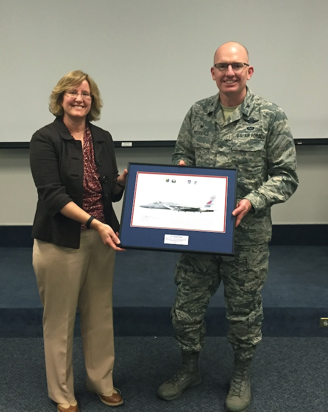 Col. Paul T. Fiztgerald, 142nd Fighter Wing commander, presents Dr. Rosemary King with a litho in appreciation for her two-day training on speech writing and delivery techniques held at Portland Air National Guard Base, Ore., Dec. 17, 2015.  King's presentation skills training is the most recent contribution to the Wing's ongoing mentorship program. (U.S. Air National Guard photo by 1st Lt. Chelsi Spence, 142nd Fighter Wing Public Affairs)