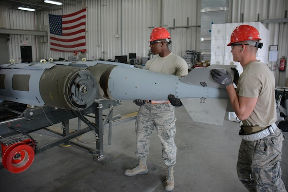 Senior Airman Christopher Haynesorth (left) and Staff Sgt. Daniel Eisenhart (right) both members of the 379th Expeditionary Maintenance Squadron Munitions Flight, install a tail kit on a 2,000-pound joint attack direct munition at Al Udeid Air Base, Qatar Dec. 17. Eisenhart, a native of Hanover, Pennsylvania, and Haynesworth, a native of Richmond, Virginia, are part of a record-setting munitions team that has built nearly 4,000 bombs since July 2015. (U.S. Air Force photo by Tech. Sgt. James Hodgman/Released)