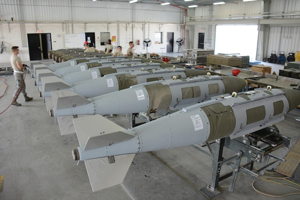 A dozen 2,000-pound joint direct attack munitions sit inside a warehouse at Al Udeid Air Base, Qatar Dec. 17. The bombs were built by hand by airmen from the 379th Expeditionary Maintenance Squadron's Munitions Flight. The Munitions Flight has built nearly 4,000 bombs since July 2015. (U.S. Air Force photo by Tech. Sgt. James Hodgman/Released)