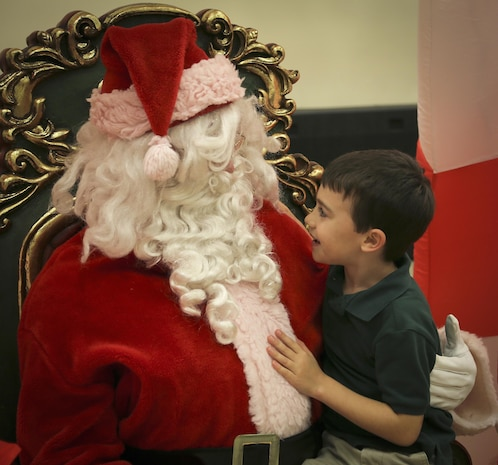 A child interacts with Santa Clause during a holiday party aboard Marine Corps Air Station Beaufort Dec. 12. Headquarters and Headquarters Squadron held the event for Marines, sailors, and their families to promote camaraderie and foster the holiday spirit within the unit. Games and activities were set up for families and children to participate in, along with a dessert contest, ugly sweater contest, and a raffle.