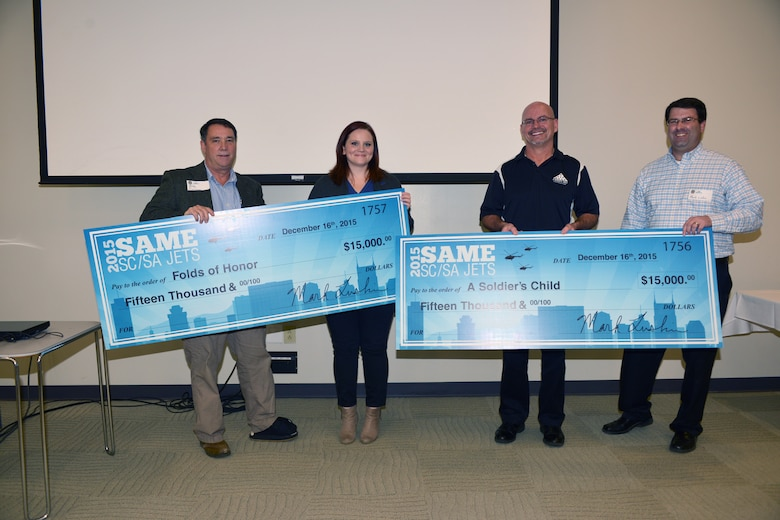 """(Left) Mike Cochrane, a member from the Nashville Post of the Society of American Military Engineers presents  (left) Crissie Carpenter from the """"Folds of Honor"""" Foundation a check for $15,000, and  (far right)  outgoing President Mark Luskin, presents Daryl Mackin from """"A Soldier's Child Foundation"""" with a check also for $15,000 during an installation ceremony in the Tennessee Engineering Center at the Adventure Science Center Dec. 16, 2015."""