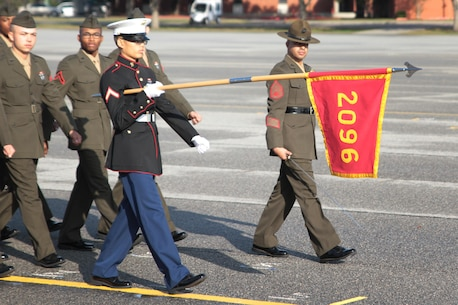 Pfc. Wanaboon B. Louangrath marches across the parade deck with his platoon's guidon, Dec. 18, 2015, at Marine Corps Depot Parris Island, S.C. Louangrath completed bootcamp as an Honor Graduated. Louangrath, a native of Spartanburg, S.C. was recruited by Sgt. Cory A. Brown at Recruiting Station Spartanburg. (Official Marine Corps photo by Cpl. Diamond N. Peden/Released)