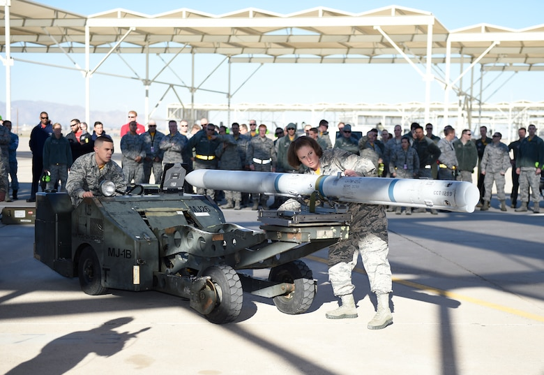 (left to right) Airman 1st Class Matthew Wolfe and Staff Sgt. Amy Zmakl, 61st Aircraft Maintenance Unit weapons load crew members, prepare to load an F-35 Lightning ll during the 4th quarter weapon's loading competition Dec. 18 at Luke Air Force Base, Ariz. This quarter featured the first time the F-35 was used in the competition against the F-16 Fighting Falcon at Luke. Three man crews from the 61st AMU, 309th AMU, 310th AMU, and the 425th AMU went head to head to earn this quarters win. (U.S. Air Force photo by Staff Sgt. Staci Miller)