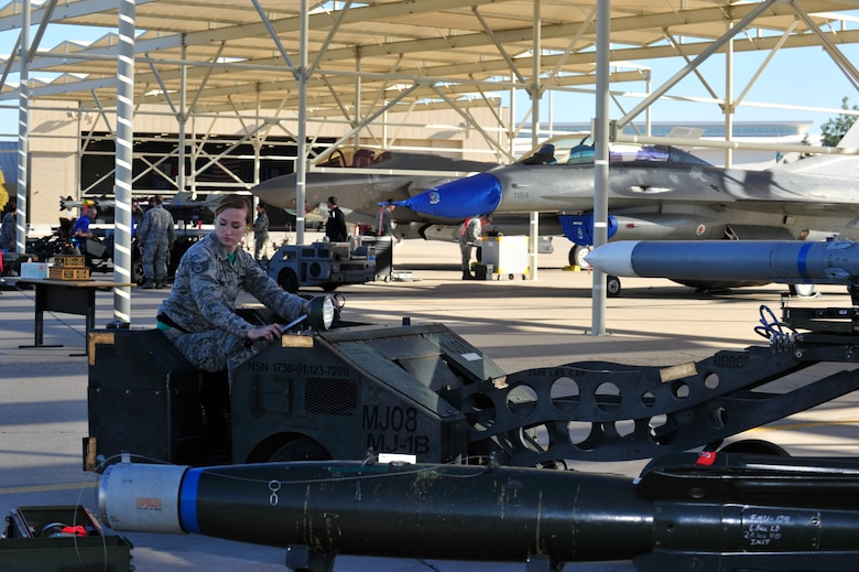 Staff Sgt. Cally Hatrick, 310st Aircraft Maintenance Unit weapons load crew member, prepares to load an F-16 Fighting Falcon during the 4th quarter weapon's loading competition Dec. 18 at Luke Air Force Base, Ariz. This quarter featured the first time the F-35 Lightning ll was used in the competition against the F-16 at Luke. Three man crews from the 61st AMU, 309th AMU, 310th AMU, and the 425th AMU went head to head to earn this quarters win. (U.S. Air Force photo by Senior Airman Grace Lee)