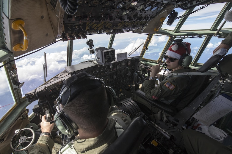 Maj. Lucas Crouch, 374th Airlift Wing, and 1st Lt. Sydney Croxton, 36th Airlift Squadron pilots, fly over Pacific Ocean Dec. 11, 2015, during Operation Christmas Drop. Every December, C-130H Hercules aircrews from Yokota head to Andersen Air Force Base to execute low-cost, low-altitude humanitarian airdrops to islanders throughout the Commonwealth of the Northern Marianas, Federated States of Micronesia, Republic of Palau. These islands are some of the most remote locations on the globe spanning a distance nearly as broad as the continental U.S. (U.S. Air Force photo by Osakabe Yasuo/Released)
