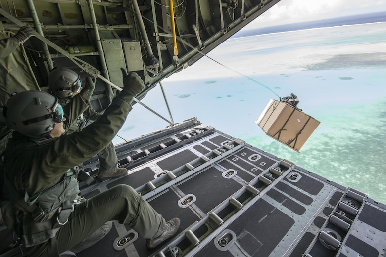 36th Airlift Squadron loadmaster and Col. TY Chamberlain, 36th Wing vice-commander, drops a low-cost, low-altitude bundle to Kayangel Atoll, Republic of Palau, Dec. 11, 2015, during Operation Christmas Drop. This year marks the 64th year of Operation Christmas Drop, which began in 1952, and is the first trilateral execution of the event with support from Japan Air Self-Defense Force and Royal Australian Air Force C-130s. (U.S. Air Force photo by Osakabe Yasuo/Released)